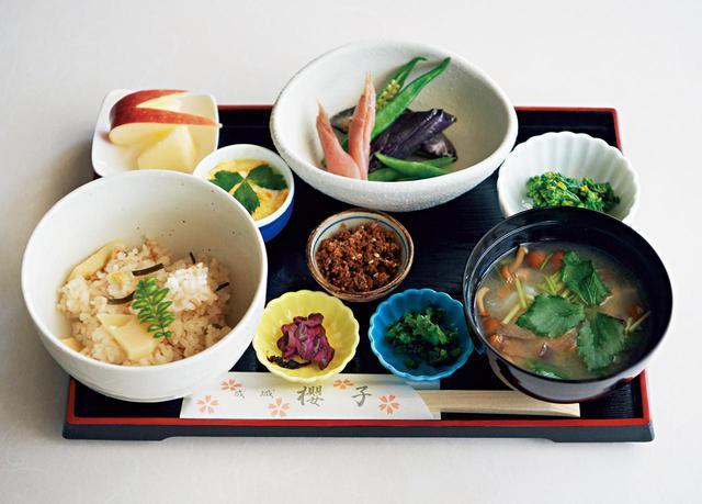 画像: この日の「おきまり」¥1,200 (右手前から時計回り) 10種類の野菜のお味噌汁(菜の花、にんじん、大根、里いも、さつまいも、ごぼう、しいたけ、こんにゃく、なめこ、三ツ葉)、漬け物2種とふりかけ、筍ご飯、ミニ茶碗蒸し、りんご、初夏の煮物(なす、みょうが、オクラ)、菜の花のおひたし。喜多見の野菜次第でメニューが替わる。これを目あてのお客さまも多く、開店と同時に売り切れることも