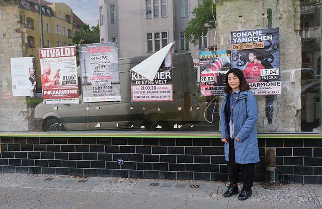 画像: 延期になったコンサートなどのポスターが貼られたウィンドウの前に立つ多和田さん。2020年春、この頃まだベルリンはロックダウン中だった