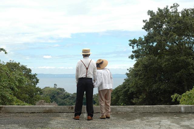 画像: 以前、ダイレクトメールに用いた写真。現在90歳を超える大家さんご夫婦にスクランプシャスの服を着用してもらって撮影。「蕗(ふき)の炊いたのを頂いたり、なんかもう親戚のおじいちゃんおばあちゃんみたいな感じのおつきあいで」。大家さんが好きすぎて、ふたりは今もこの海の家に住み、そこからSOJI BŌKENへ出かけていく。「大家さんたちは、私たちの人生の目標です」 COURTESY OF SCRUMPCIOUS