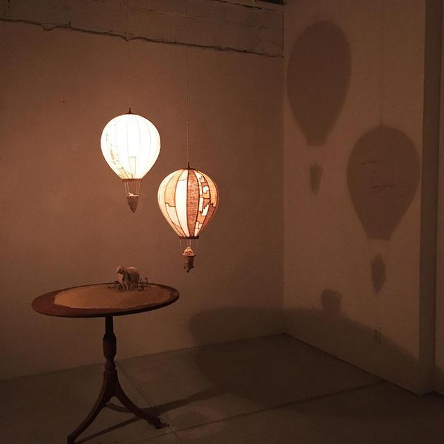 画像: 2019年11月、友人の木彫作家、西浦裕太さんが恒例とする福岡のkrank marcelloにて、ともに作った作品を発表。写真の気球は照明。木彫は西浦さん、靖さんは布部分を担当。作品は好評を得て、たくさんの人に届けられるところとなった。「自由帳」の芯の部分はこのままでよいと、背中を押してもらえたようだとふたりは言う STYLING BY KRANK MARCELLO, WOOD SCULPTURE BY YUTA NISHIURA COURTESY OF SCRUMPCIOUS