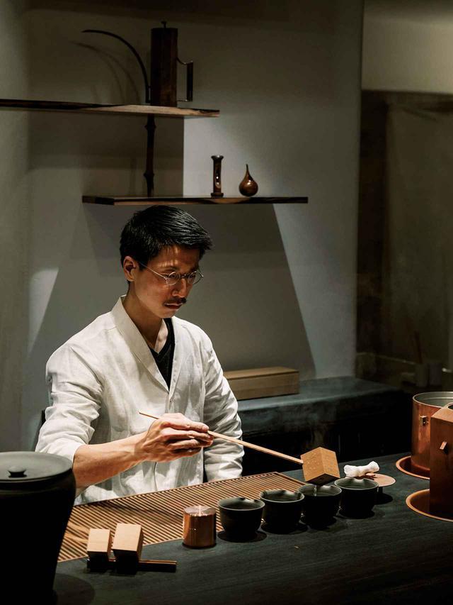 画像: 地下の茶房。炭化木材のバーカウンターで、柄杓でお湯を注ぐ茶の専門家