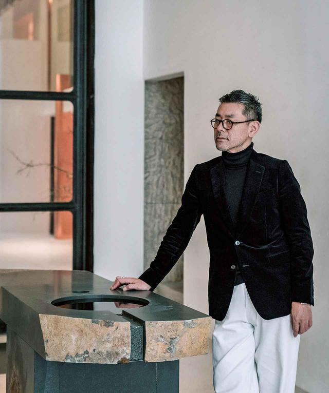 画像: プロジェクトの中心人物、緒方慎一郎。エントランスホールからつながる部屋にしつらえた伊達冠石(だてかんむりいし)から切り出した手水鉢にもたれて