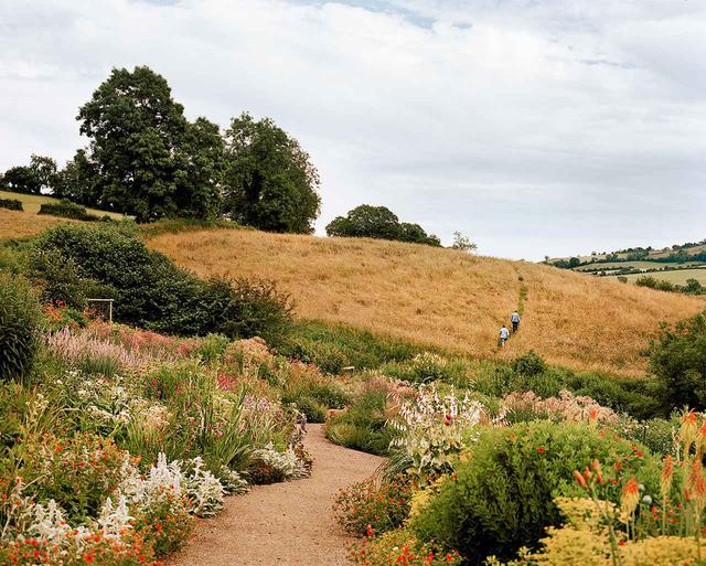 画像: 観賞用庭園からシームレスに続く野草の牧草地に向かって、草が刈られた道を進むピアソンとモーガン