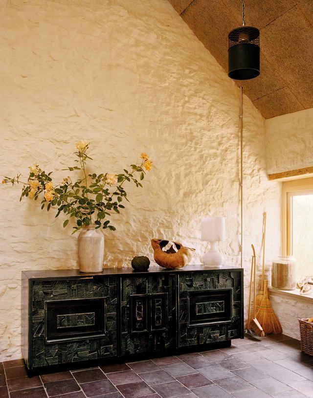 画像: 元は羊飼いの小屋だった高い天井のエントランスホール。壁には石灰塗装が施され、床には素焼きの再生タイルが敷かれている。黒塗りの木製キャビネットはミッドセンチュリー期の家具メーカー「Lane Furniture」製のヴィンテージ。残りの部屋はあとから増築したもの