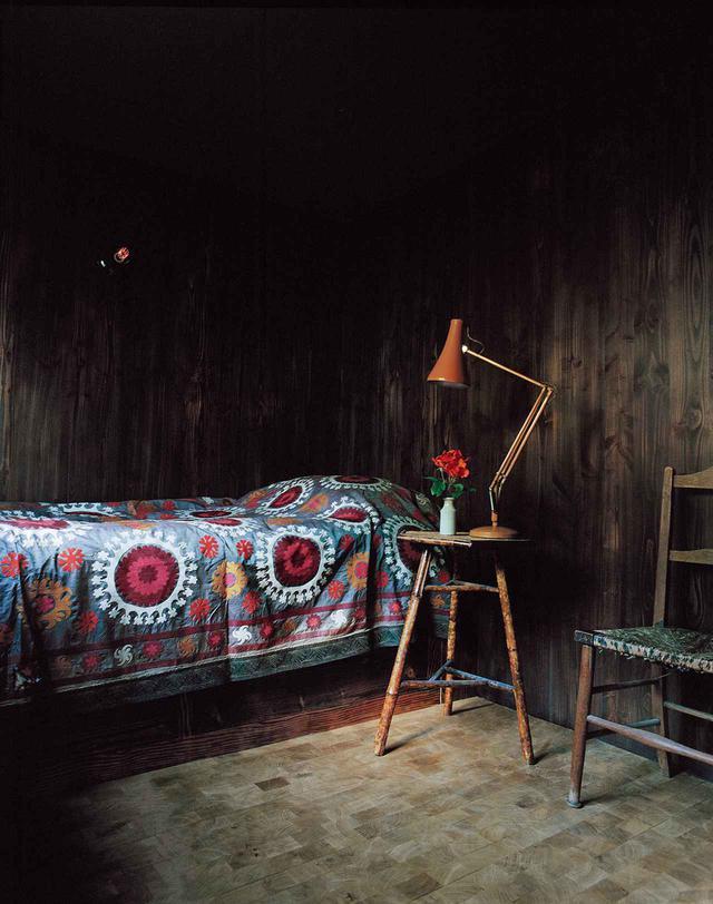 画像: 来客用寝室の黒塗りのマツの羽目板を張った壁、イングリッシュオーク材のブロックを敷き詰めた床、ヴィンテージのスザニ刺しゅうのベッドカバー