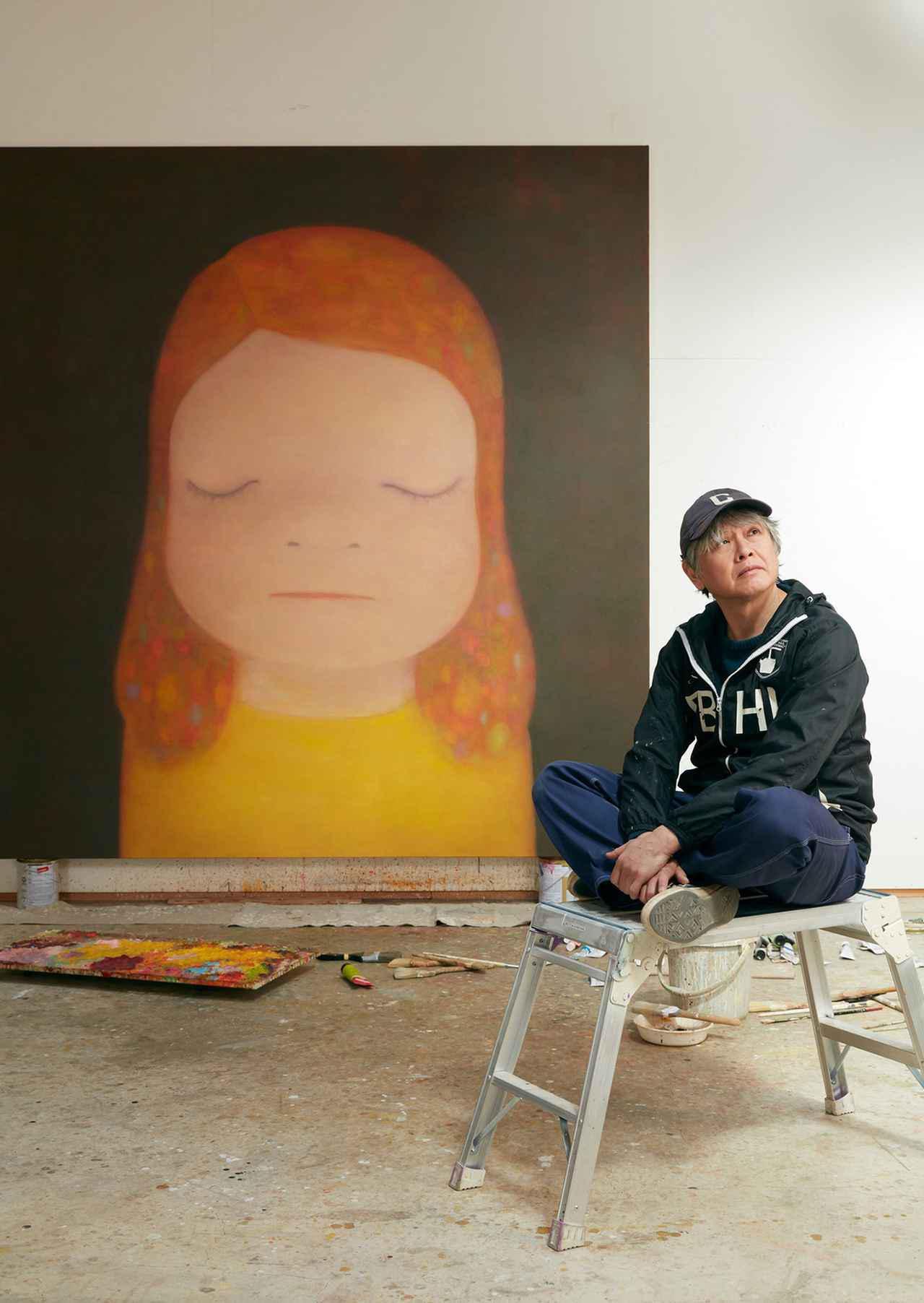 """画像: 奈良美智と、""""大きな頭の女の子""""を描いた彼の作品《Miss Moonlight》(2020年)。栃木県にある彼の自宅スタジオにて撮影"""