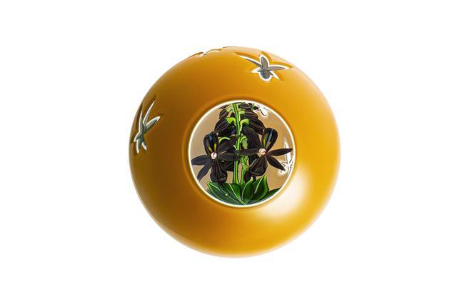 画像: ペーパーウェイト《BLACK ORCHID》 ¥607,000<H89mm、直径92mm>※ 9月発売 周囲に花弁モチーフをベベルカットで施した琥珀色のクリスタル。丸窓のなかにマザーオブパールを中央にあしらった蘭が潜む