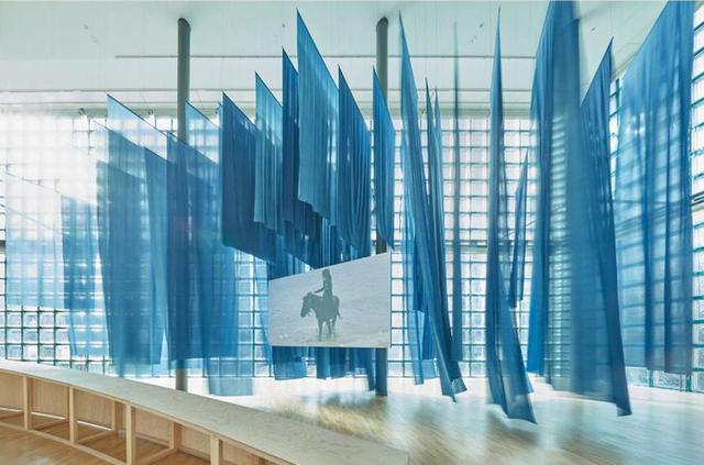 画像: 《潮》(2018)の展示風景。スクリーンを囲む青い布のインスタレーションは、沖縄在来の草木を使って染色を施すテキスタイルデザイナー、キッタユウコがデザイン。会場全体の構成は、建築家の小林恵吾と植村遥が担当している © NACÁSA & PARTNERS INC. / COURTESY OF FONDATION D'ENTREPRISE HERMÈS