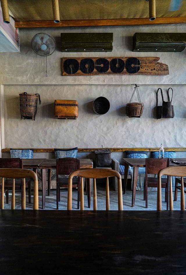 画像: ジオ カフェ ヴィンテージの木製家具、ベトナム人による工芸品の籠、灰色の壁、クラシックなブルーのモザイク柄の心地よいクッションなど、自然主義でミニマルな雰囲気のインテリアがバランス良く組み合わされた空間で穏やかな気分に