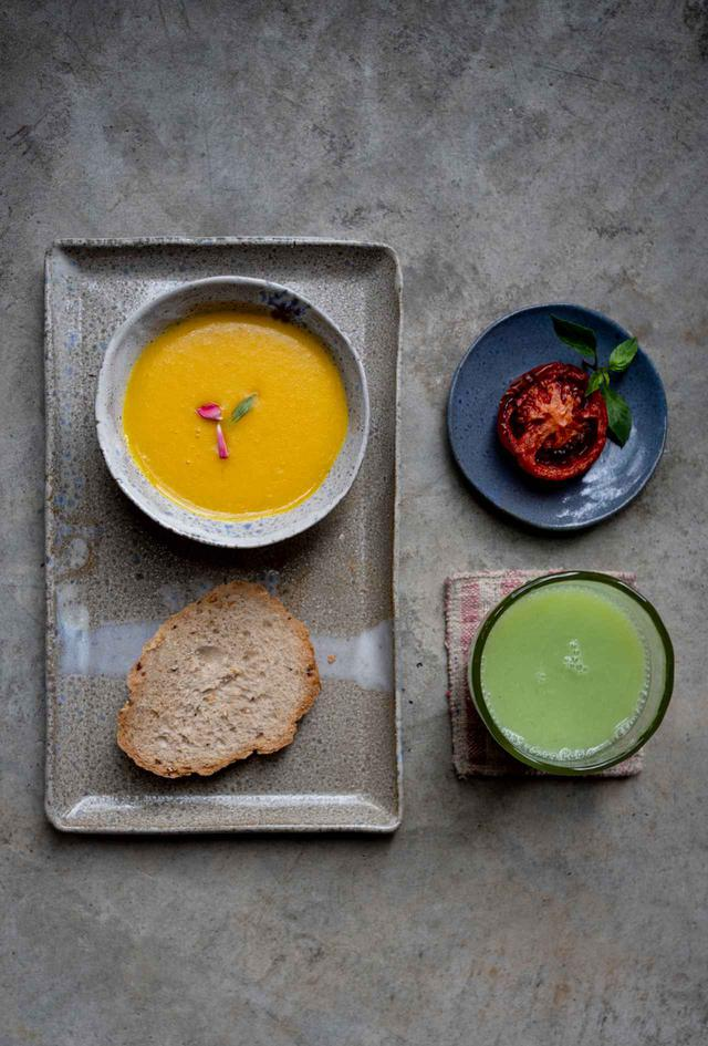 画像: 美しい陶器の皿に盛り付けられたカボチャスープ、自家製パン、焼いたトマトとフレッシュグァバジュースのヴィーガンセット。健康的なだけでなくとても美味しい