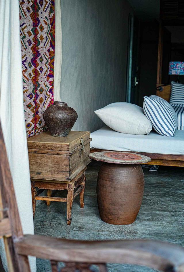 画像: 光沢のあるコンクリートの床、壁、ベッドの木枠、アンティークと手造りの陶器と布等、色と質感を混ぜ合わせた自然で心地よい雰囲気のベッドルームの光景