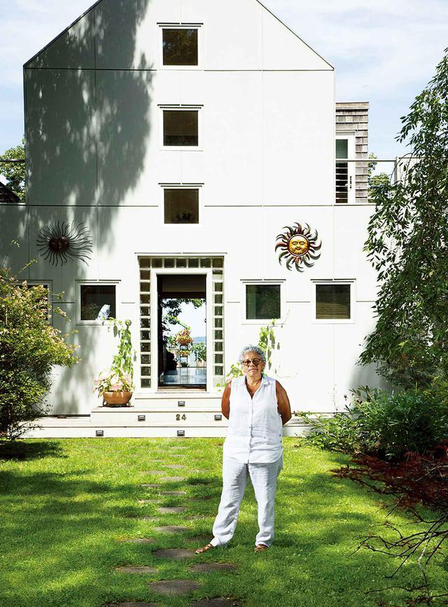 画像: 長年の住人で陶芸家のビバリー・グランジャー。彼女の両親から受け継いだ海辺の自宅の前で