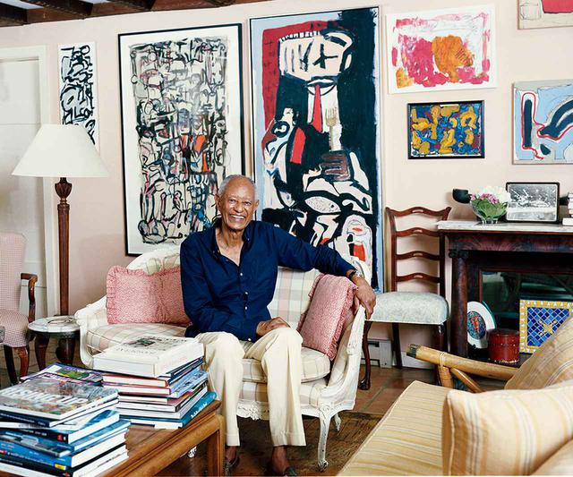 """画像: ブルックの父E.T.ウィリアムズ。ブルックの家の隣に住んでいる。部屋の壁は画家のクロード・ローレンスの作品であふれている ON WALL, FROM LEFT: CLAUDE LAWRENCE, """"CITIZENRY,"""" 2015, ACRYLIC ON PAPER COPYRIGHT ELNORA INC.; CLAUDE LAWRENCE, """"THE RITZ,"""" 2016, OIL ON CANVAS, COPYRIGHT ELNORA INC."""