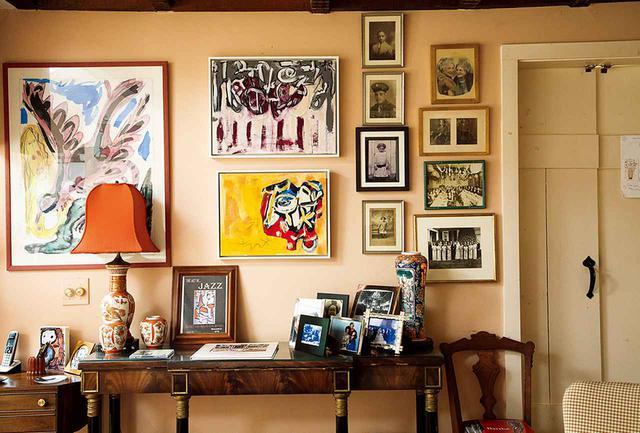"""画像: E.T.ウィリアムズ所有の、19世紀に建てられたイーストヴィルの家に飾られている家族の写真と、クロード・ローレンス、ソーントン・ダイアルが描いた作品 THORNTON DIAL, WATERCOLOR AND INK ON PAPER; CLAUDE LAWRENCE, """"SATURDAY SUBDUED,"""" 2014, ACRYLIC ON CANVAS, COPYRIGHT ELNORA INC.; CLAUDE LAWRENCE, """"IT'S OVER AND YET,"""" 2014, ACRYLIC ON CANVAS, COPYRIGHT ELNORA INC."""