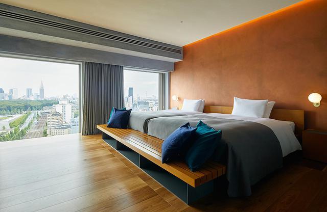 画像: 17階に一室だけあるスイートルーム<94.7㎡>の寝室。窓からは緑の代々木公園を通して新宿高層ビル街を見渡せる