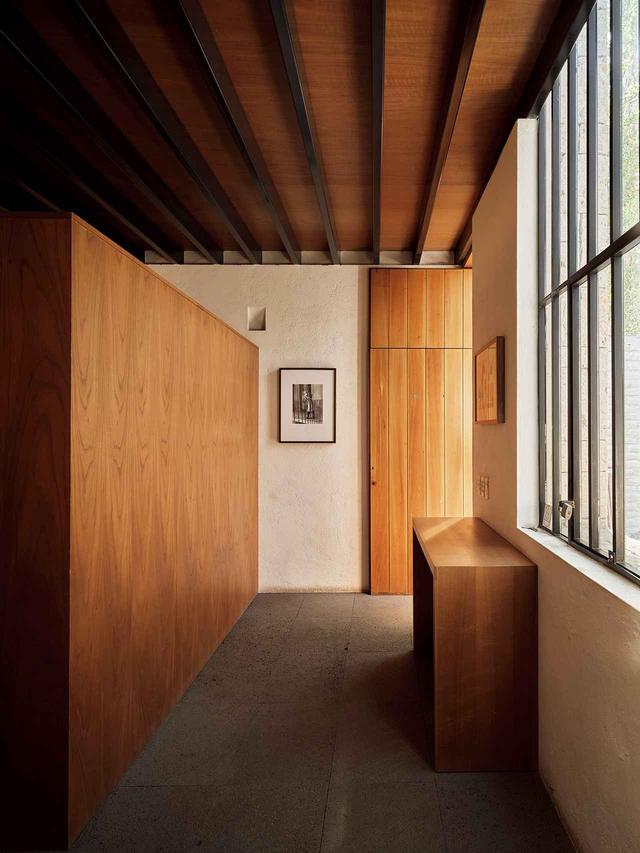 """画像: 2008年に完成した建築家セルジオ・オルティスのスタジオのエントランス部分。ざらざらした漆喰壁、鋼鉄製の窓、火山岩の床、シダー材の木工製品 PHOTO ON WALL: MANUEL ÁLVAREZ BRAVO, """"EL ENSUEÑO"""" (""""THE DAYDREAM""""), 1931, PERMISSION COURTESY OF ARCHIVO MANUEL ÁLVAREZ BRAVO, S.C./ASOCIACIÓN MANUEL ÁLVAREZ BRAVO, A.C. AND ROSEGALLERY"""