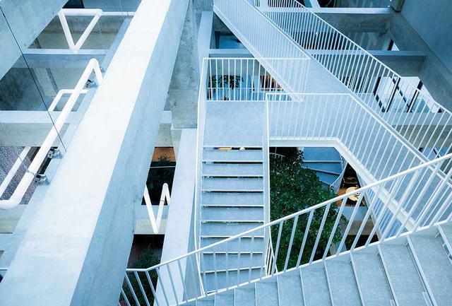画像: 最上階となる4階から見下ろした吹き抜け空間。客室は吹き抜けを囲む通路沿いに配置され、階段と通路をつなぐブリッジとレアンドロ・エルリッヒの《Lighting Pipes》が迷路のような空間をつくり出す