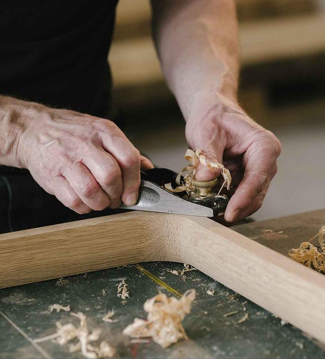画像: 工房にて。チェアの前脚にあたるバーツの側面をカンナで整える職人の手元 PHOTOGRAPH BY MAXIME VERRET, © HERMÈS2020