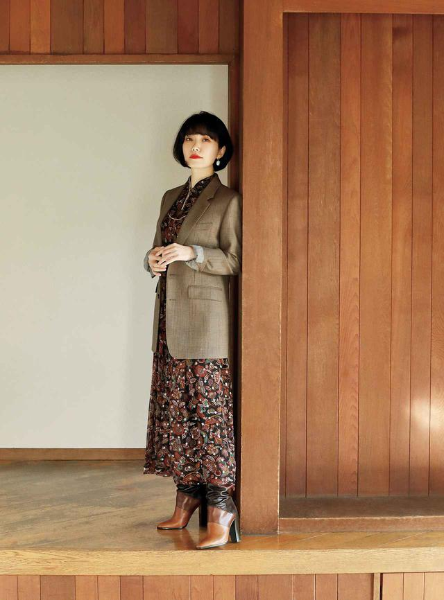 画像: 柔らかいフラワープリントドレスに合わせたのは、かっちりとしたスタンダードなテーラードジャケット。ベージュベースのチェックにミドル丈がモダンな薫りを醸し出す。硬軟を織り交ぜたジャケットスタイル ジャケット¥324,500、ドレス¥445,500、イヤリング¥95,700、ブーツ¥258,500/セリーヌ バイ エディ・スリマン セリーヌジャパン TEL. 03(5414)1401