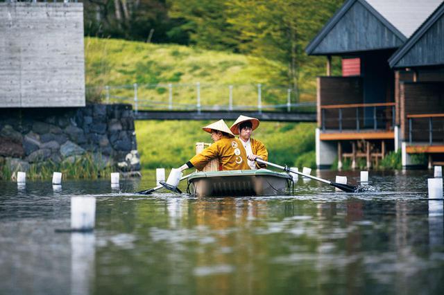 画像: 「星のや軽井沢」の施設内の池に照明器具をひとつひとつ設営するスタッフ