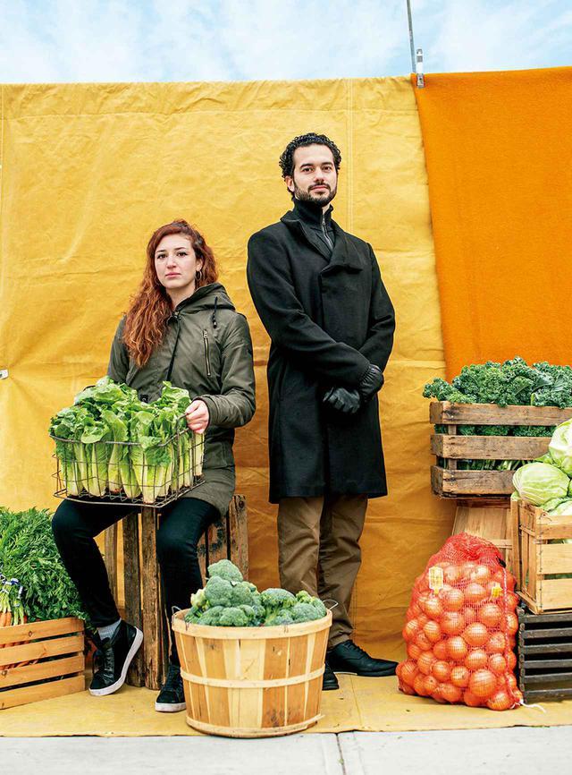 画像: (左より)ニューヨーク市のアーバン・ジャスティス・センターで露天商プロジェクトを担当するカリーナ・カウフマン=グティエレスとモハメッド・アティア。ブルックリンにあるローランド&アナ・ペレズの野菜スタンドにて。2021年1月15日撮影 SET DESIGNER'S ASSISTANT: HARRY SMITH