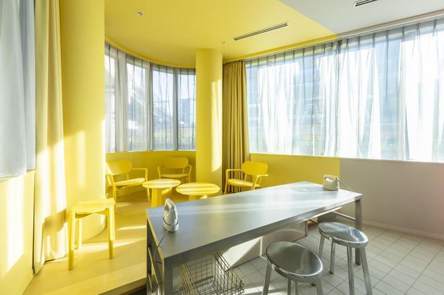 画像: 2階にあるランドリーサービスルームは黄色とグレーの配色。滞在者が自由に使える洗濯機、乾燥機、アイロン台のほか、自動販売機も設置