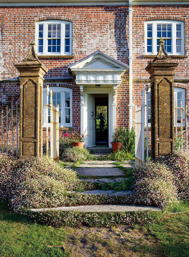 画像: 17世紀に建てられた館の正面エントランスは、広大な庭へとつながる。エリゲロンが両側に咲き乱れる門の向こうには、自然のままの英国の田園風景が広がっている