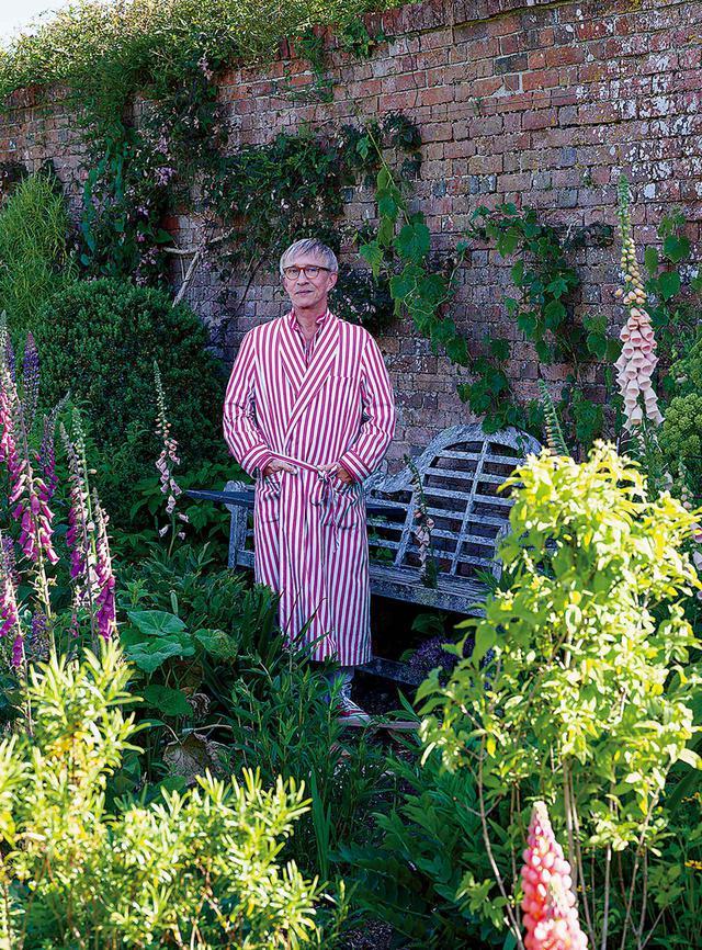画像: 穏やかにくつろぐジャスパー・コンラン。壁に囲まれた庭の中、背高のジギタリスの穂先の間にて