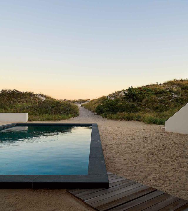 画像: ベネットがハンプトンズで手がけた数少ない家のひとつ。青石を敷き詰めたプールは砂に囲まれ、その先にはビーチが広がる