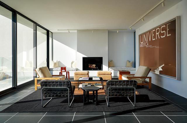 """画像: リビングルームの壁にはエド・ルシェの作品(2016年作)、スレートの床にはハンス・ウェグナーやシャルロット・ペリアンの椅子が並ぶ。 PAINTING ON WALL:ED RUSCHA, """"UNIVERSE WITH WRINKLES,"""" 2016, ACRYLIC ON CANVAS © ED RUSCHA. COURTESY OF THE ARTIST AND GAGOSIAN"""