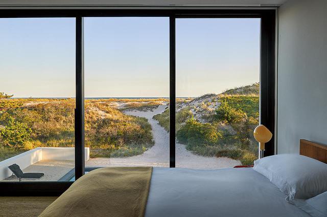 画像: メインベッドルームからは、プールと砂浜に続く海原が見渡せる。ランプはガエ・アウレンティ作