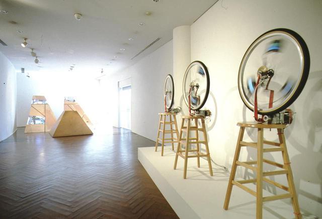 画像: 《デュシャンピアナ:自転車の車輪1、2、3》と《三つの山》の展示風景(原美術館、1992年) PHOTOGRAPH BY YOSHITAKA UCHIDA COURTESY OF SHIGEKO KUBOTA VIDEO ART FOUNDATION; © ESTATE OF SHIGEKO KUBOTA