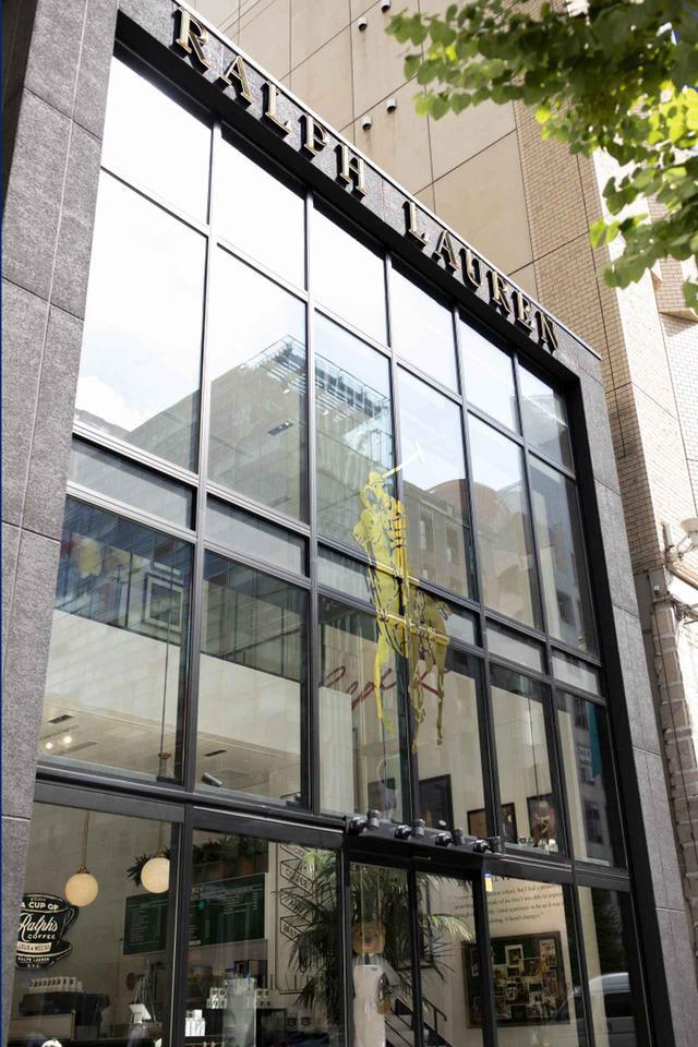 画像: 中央通りに面したガラス張りのファサードにはゴールドに輝くロゴマークが