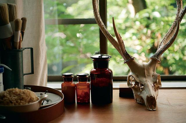 画像: アトリエには、道具のほか着想源になるオブジェも並ぶ。ガラス瓶に入っているのは、革や紙の接着に使うさまざまな種類の糊