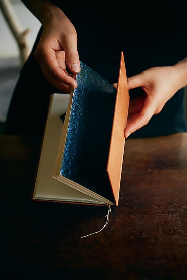 画像: 樋口の愛読本のひとつ、サン=テグジュペリの『人間の土地』を着想源にしたノート《サン=テグジュペリ人間の土地》。レザーのしぼが砂漠を、マーブルの見返しが漆黒の闇のなかで輝く星々を連想させる。ファッションブランドamachi. (アマチ)のデザイナー吉本天地が所有し、創作用のノートとして愛用