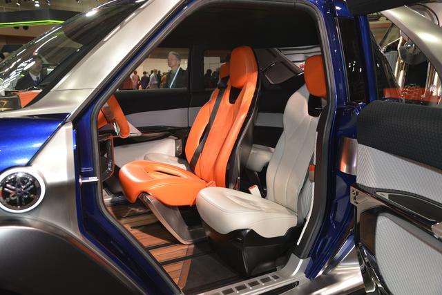 画像: このクルマの最大の特徴はシートのレイアウト。オレンジ色の運転席の後方にもう一座シートがある。