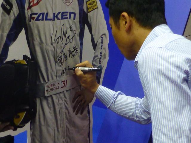 画像: 自身の等身大パネルにサインを入れる室屋選手。
