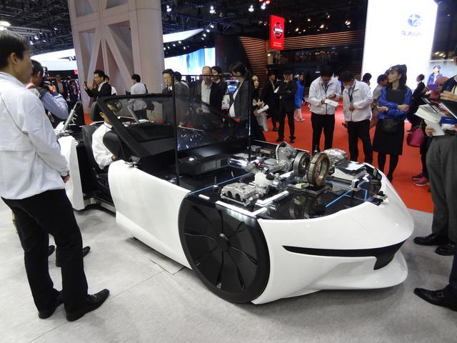 画像: ブースの中央にあるショーケースカー。自動運転に関係するパーツがわかりやすく展示されている。