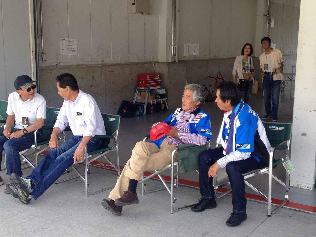 """画像: 残念ながら、RGB500のシリンダーに焼きつきが発生し、日曜日は走行できなくなってしまった水谷さん(右)。日曜日はファンサービスに励みつつ、日本のレジェンドたちのアテンド役をしていました。左からモトクロス界のレジェンド吉村太一さん、""""シャケさん""""ことexスズキ・ヤマハの名ライダー、河崎裕之さん。そしてスズキの重鎮岡本さんです。"""