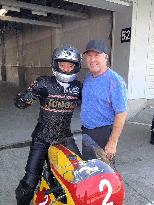 画像: 1966年ブリヂストン90にまたがるジャングルスクーターズ店主の古田さん(左)と、ケニー・ロバーツ。2015年の鈴鹿サウンドオブエンジンでの一コマですが、この時パドックにはトーハツランペットCA2もいて、「おー!! 懐かしい!! 俺が最初に乗ったバイクはコレだったんだよ!!」と語っていました。 soundofengine.lrnc.cc
