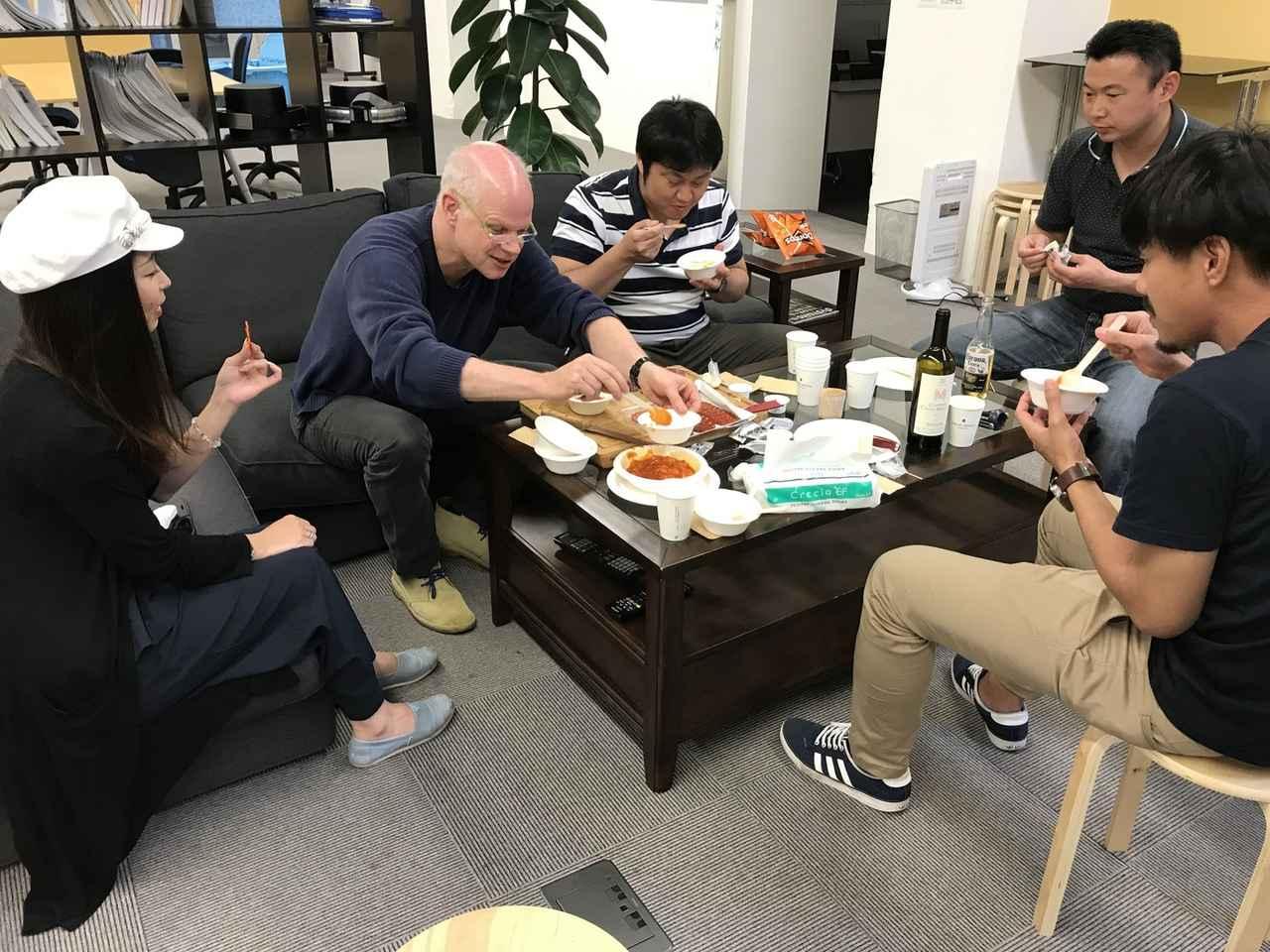 画像: 写真は先週のハッピーフライデーの様子。スチュアート(弊社代表)がエビチリをみんなに取り分けてくれています。