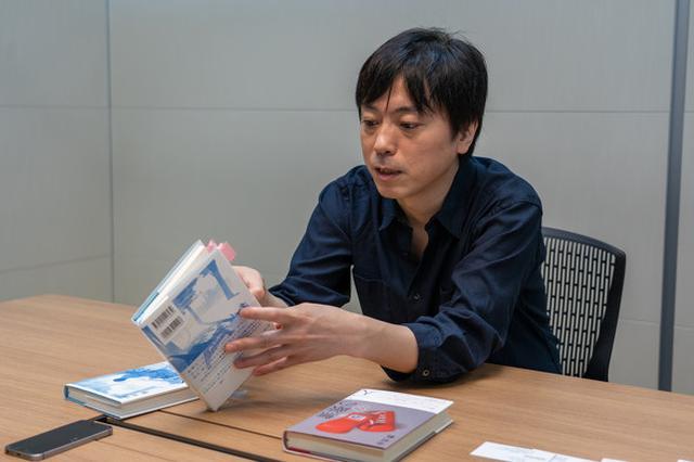画像: 多くの付箋が付いた最新作『サバティカル』を手に取る中村氏