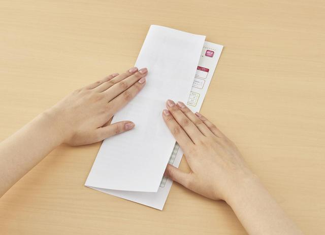 画像: テープで情報を隠し、さらに折り畳んで処分する。