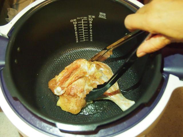 画像: 塩とこしょうで下味をつけた骨付きの鶏肉を、皮のほうを下にして焼き色がつくまで焼く。