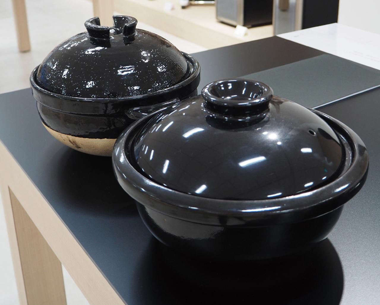 画像: 奥が元祖のかまどさん、手前がかまどさん電気の土鍋。元祖のほうがフタを含めてやや高さがあり、全体的に表面がザラザラしているが、電気の土鍋のほうは滑らかな作りだ。