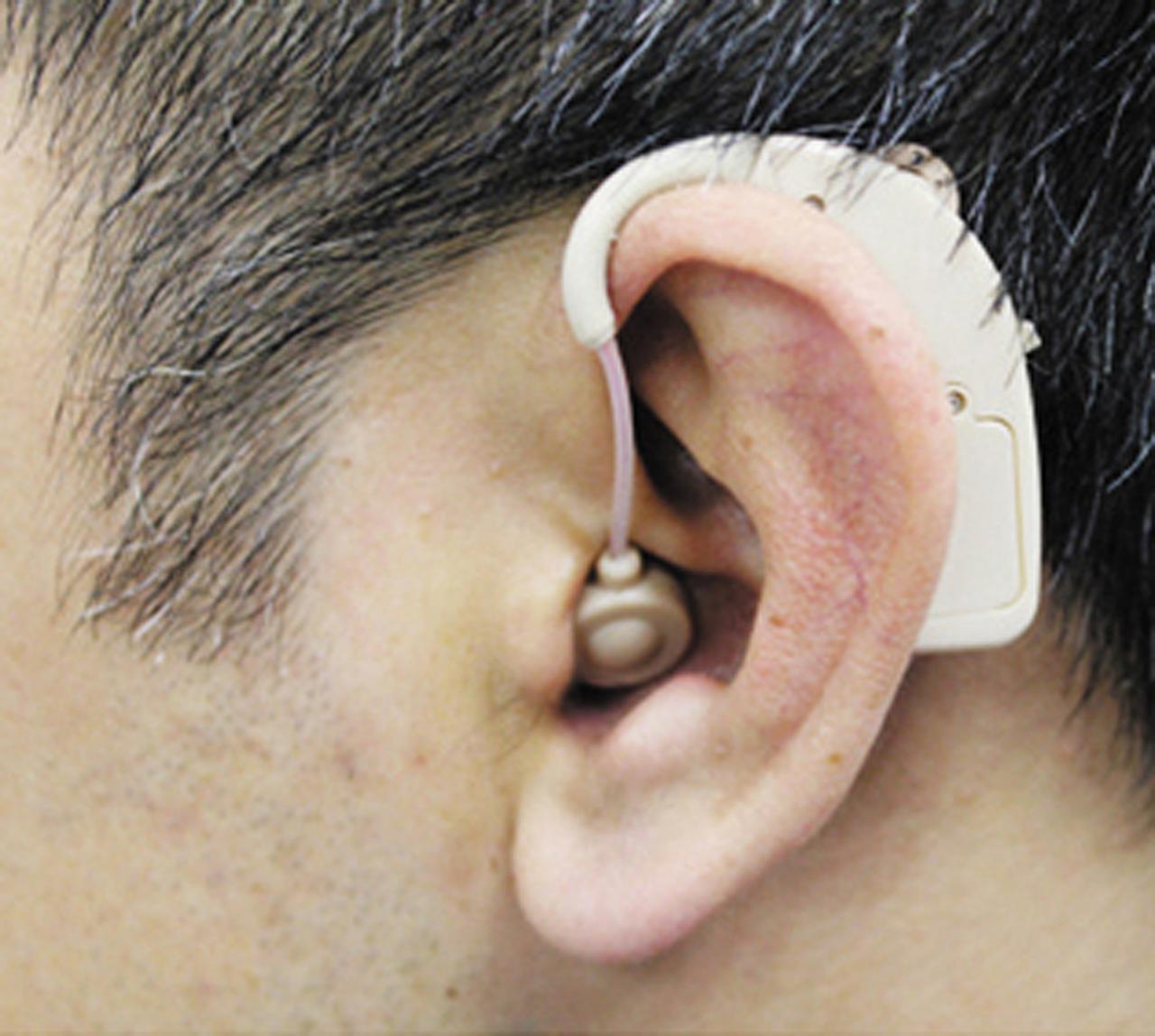 画像: 耳にかけた状態。本体が少し耳からはみ出してしまうサイズだ。
