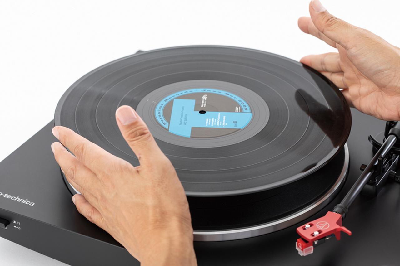画像: 盤面に手を触れないように注意しながら、スピンドルに盤の穴を合わせてレコードを置く。EP盤はアダプターを使う。