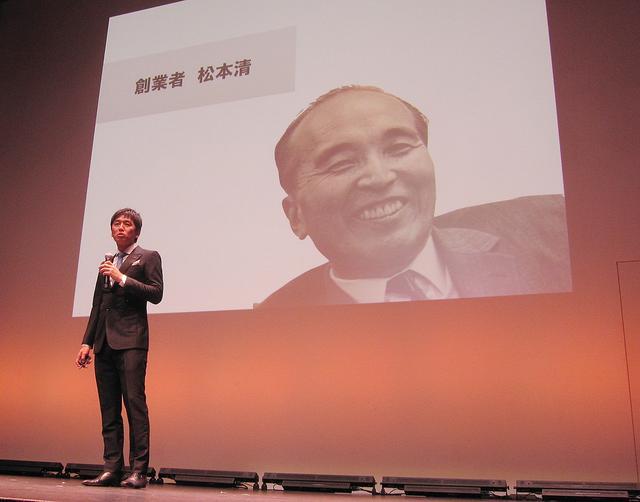 画像: 松本貴志氏は1937年の創業から現在の活動までをスピーチ。