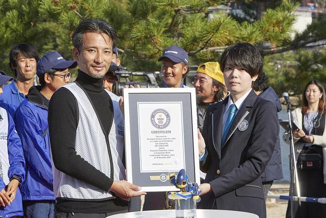 画像: ギネスレコードの認定証を受け取る高橋智隆氏(左)。ギネス世界記録公式認定員・佐藤コーマ氏(右)。