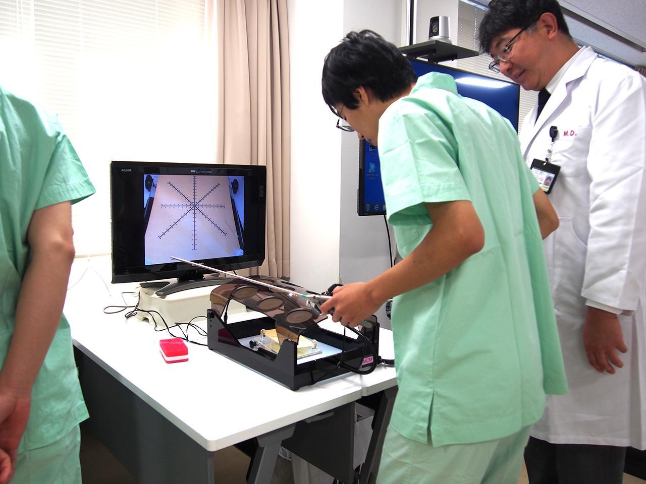 画像: 中村雅敏医師にアドバイスをもらいながら実際に、腹腔内視鏡を体験。力加減や手先の器用さに加え、集中力も必要だ。